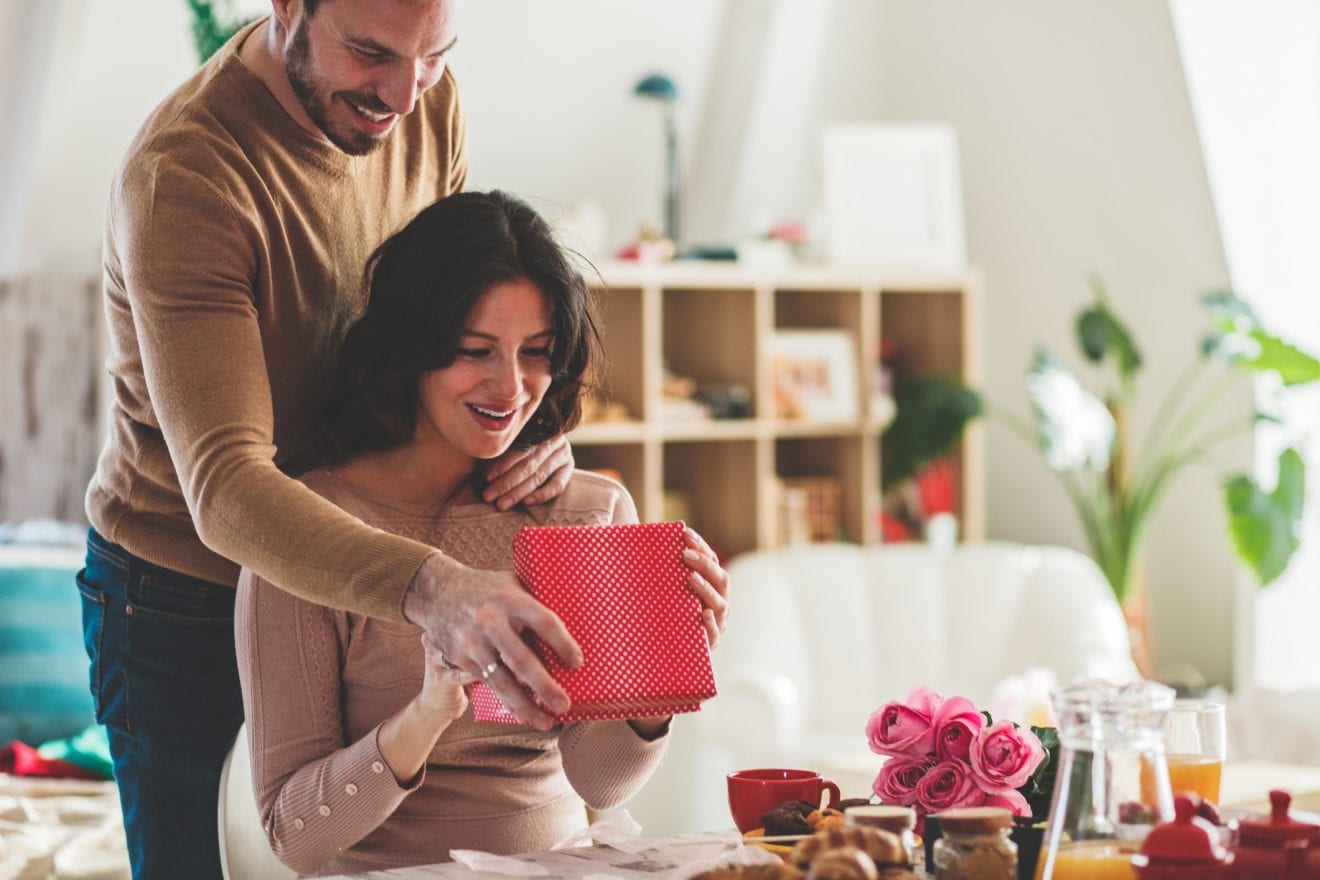 Smiling mid adult man surprising his girlfriend with a gift she is opening on a romantic date.