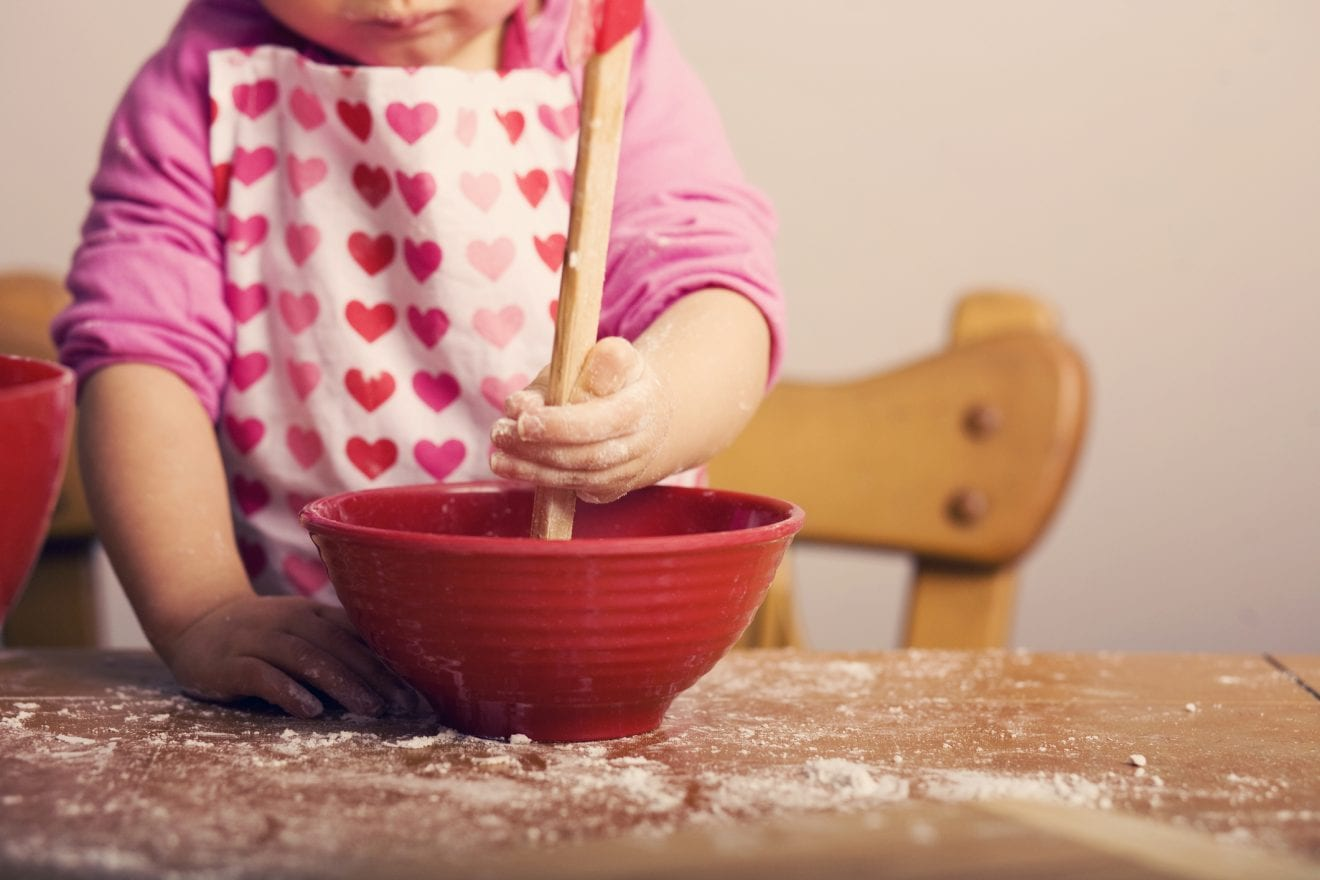Little Girl Mixing Ingredients in Red Bowl.
