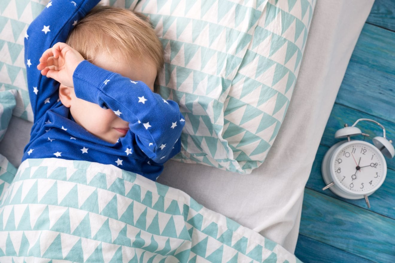 Three years old child crying in bed. Boy hiding and closing eyes with hands.