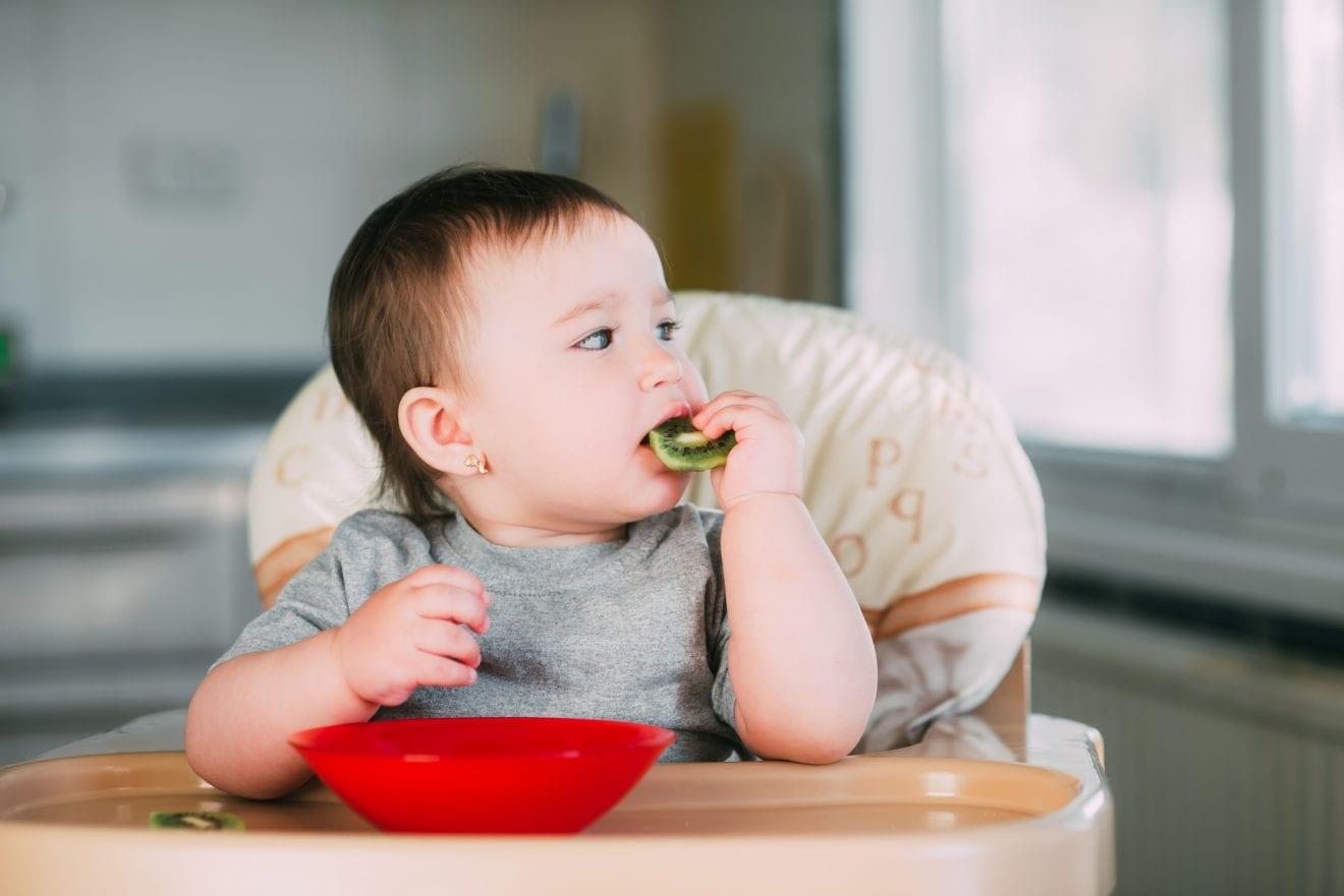 little girl on a high chair eating kiwi