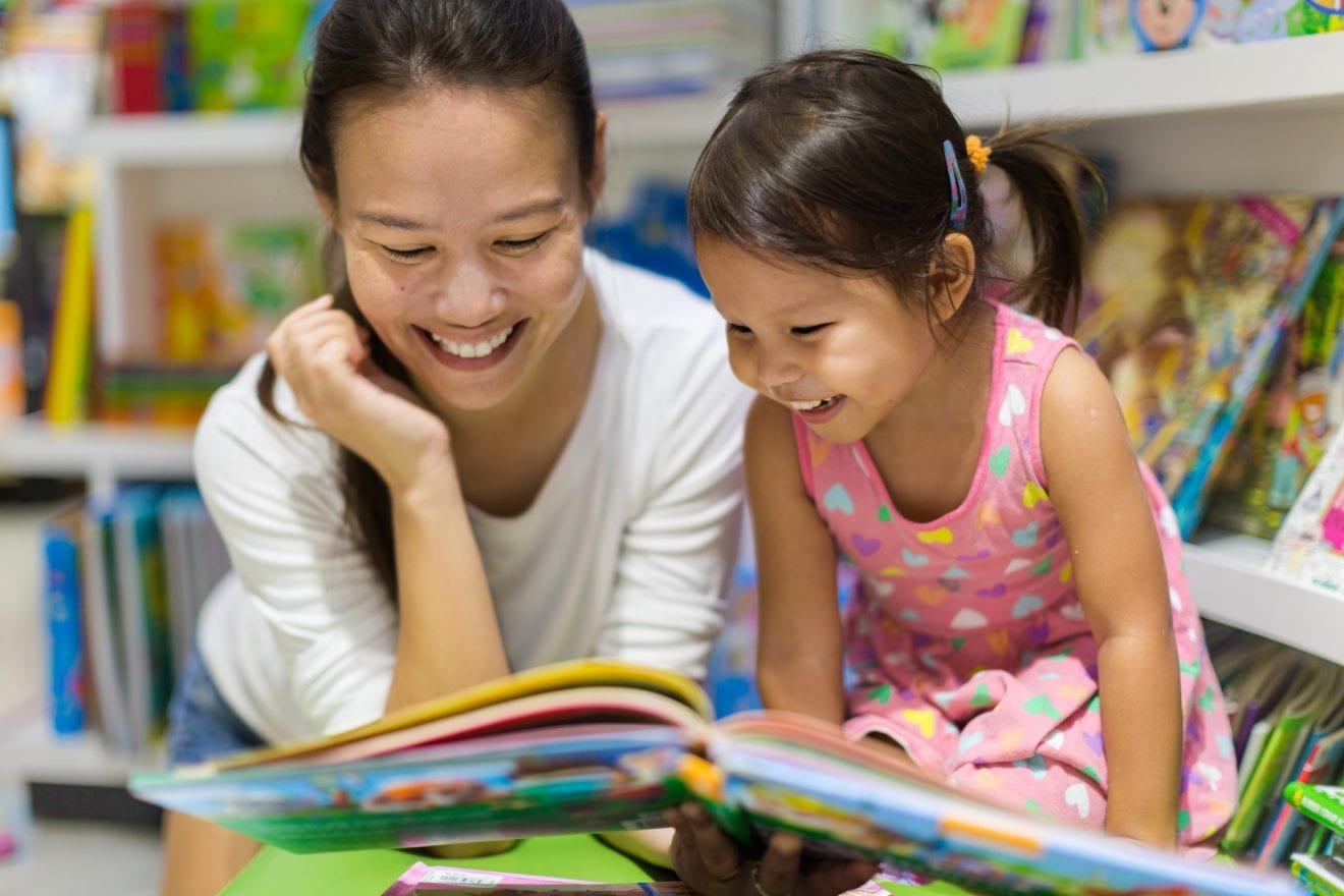 Parent and child reading books together for homeschooling.