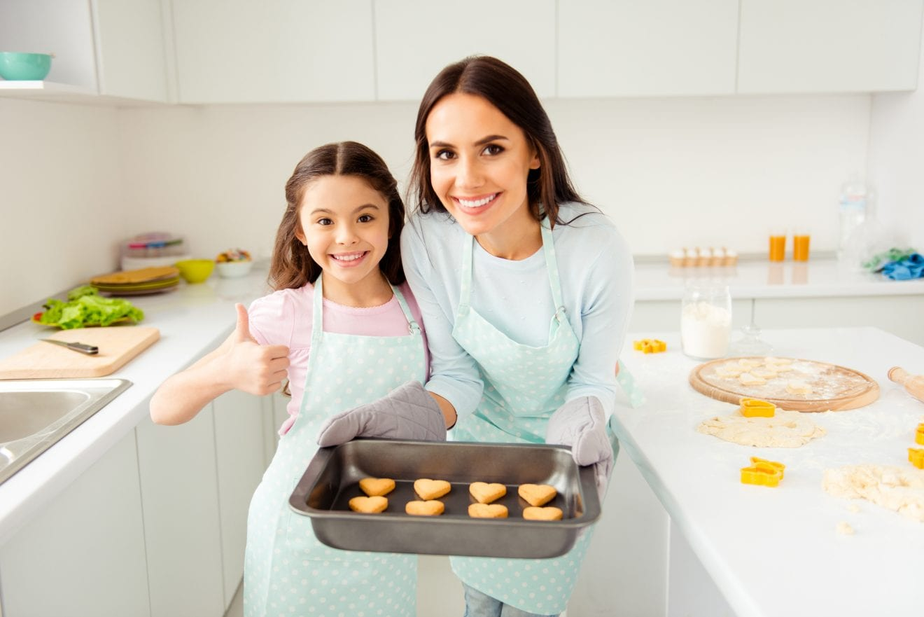 Charming adorable attractive beautiful brunette caucasian kind smiling young mum and her small little offspring daughter, wearing apron, showing thumb up, holding prepared cookies in light kitchen.