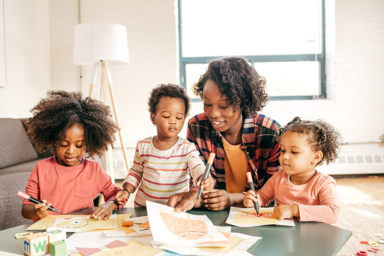 A mom with her toddlers creating at the table with paper and markers.