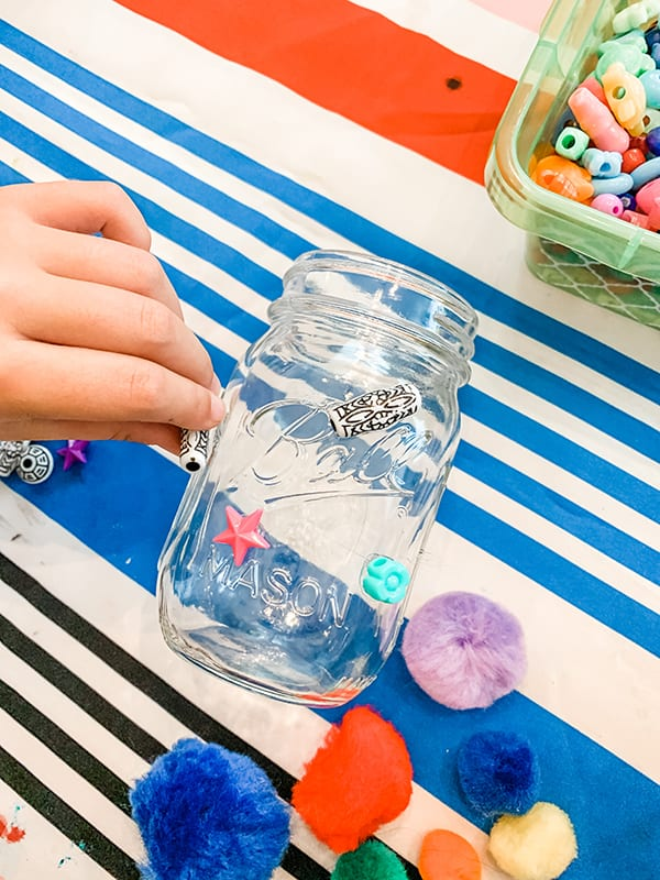 A mason jar on a table being decorated
