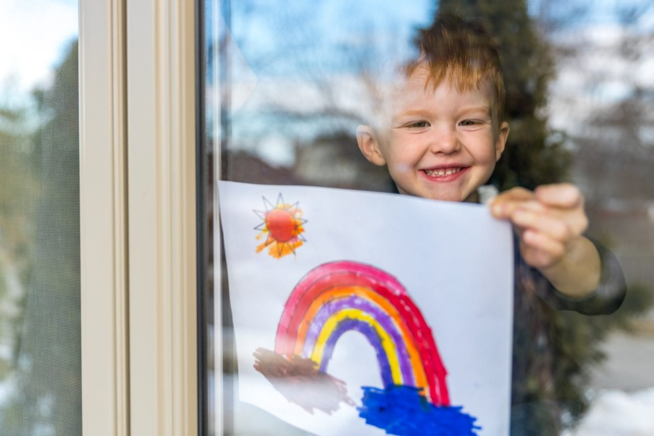 Young Boy sticking his drawing on home window during the Coronavirus Covid-19 crisis, Many people are putting a rainbow to tell neighbors that people inside this house are ok.