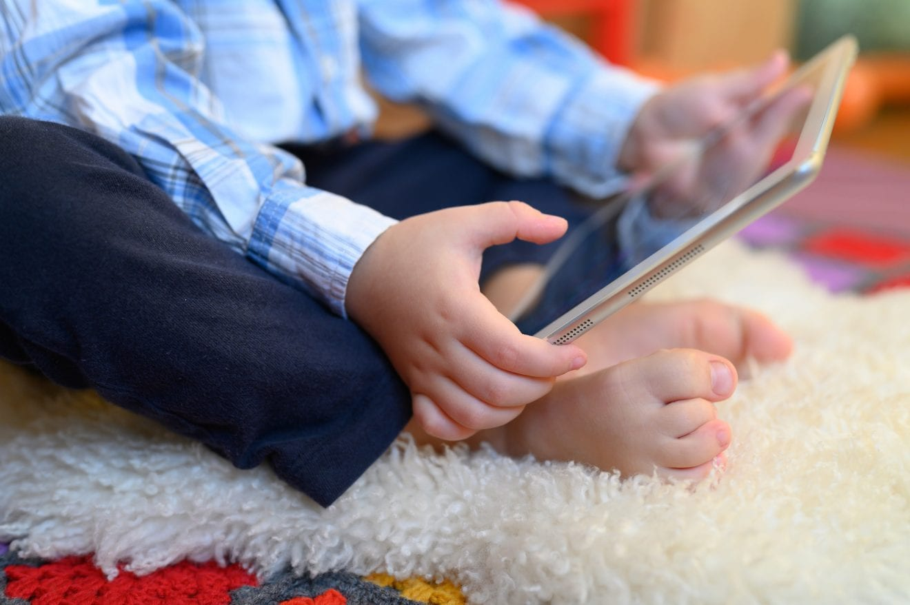A little boy sitting on the floor playing on an iPad or smart tablet.