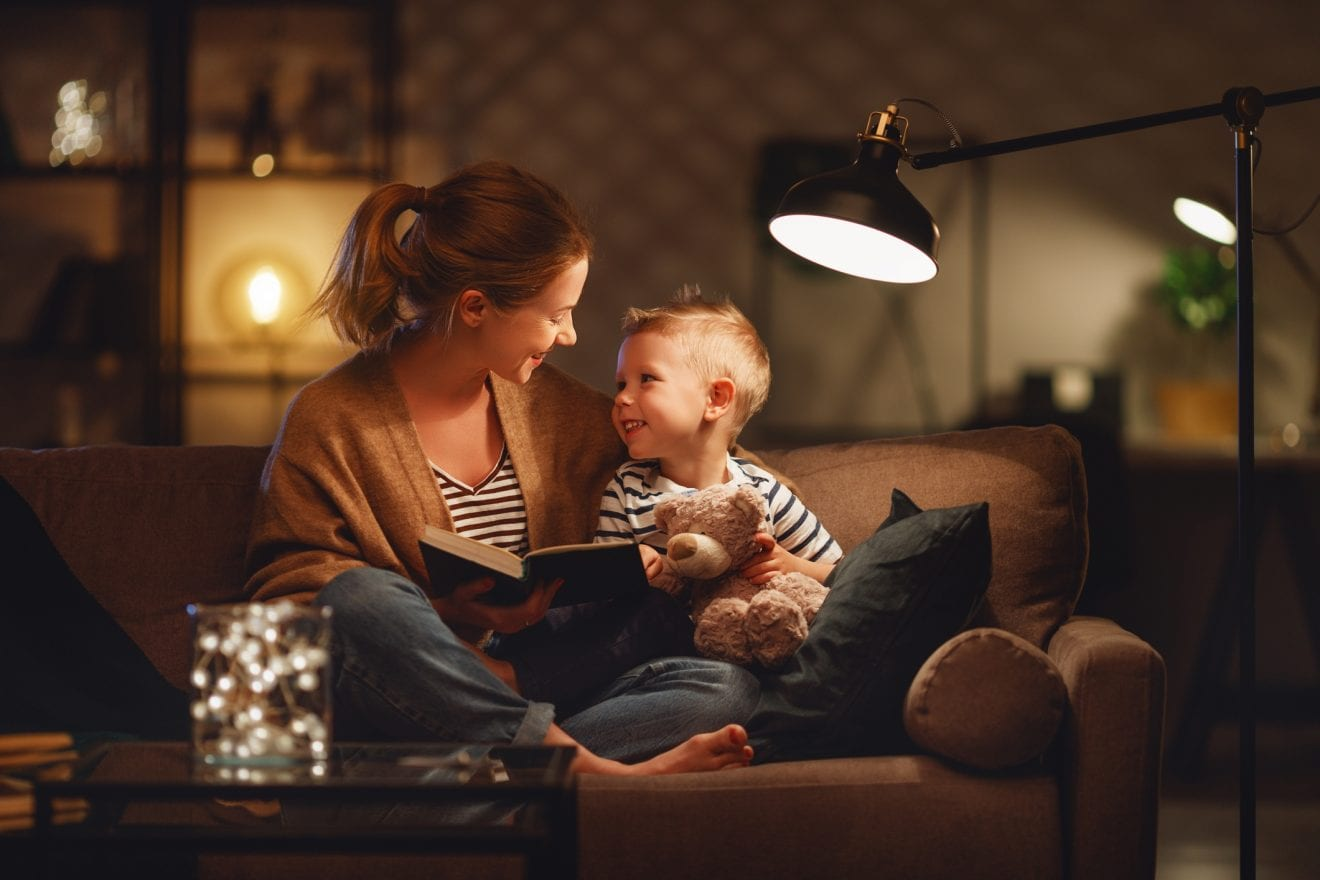 Family before going to bed mother reads to her child son book near a lamp in the evening.
