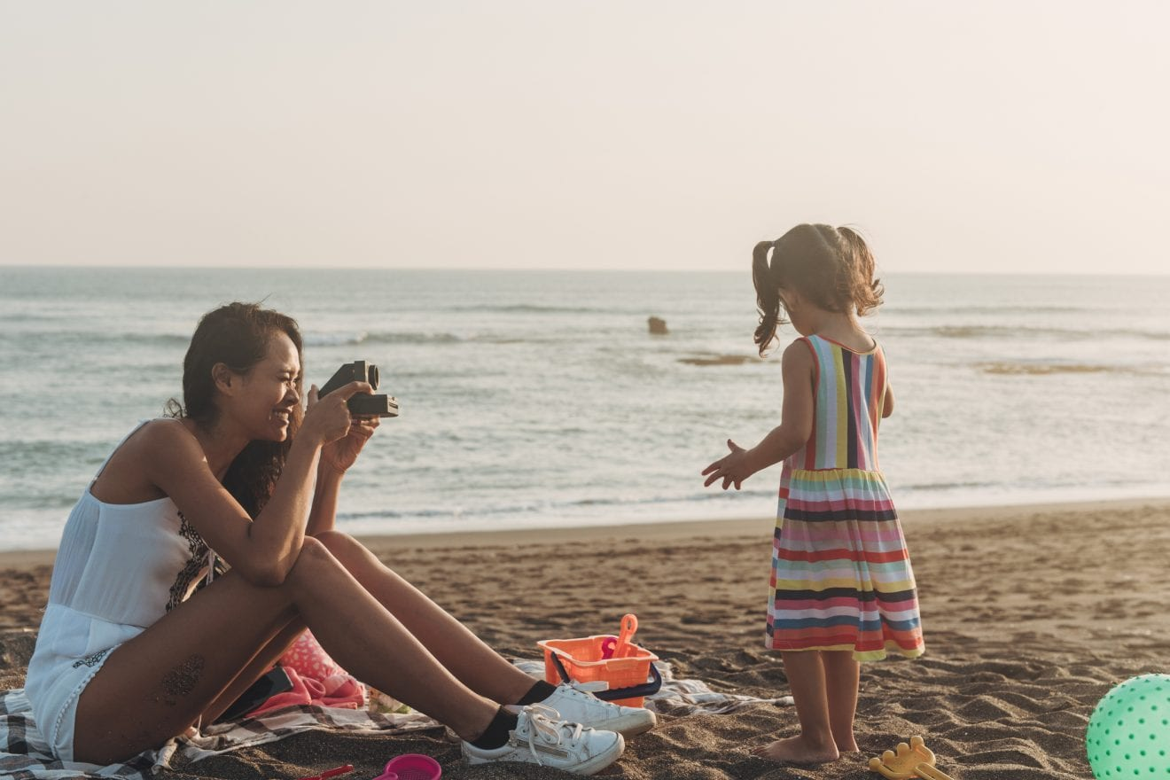 Mother photographing little daughter at the beach with instant camera.