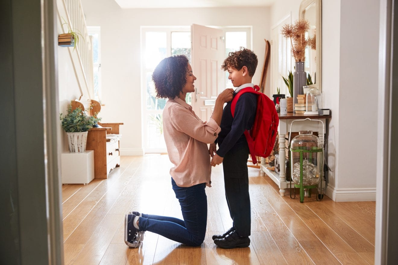 Mother At Home Getting Son Wearing Uniform Ready For First Day Of School