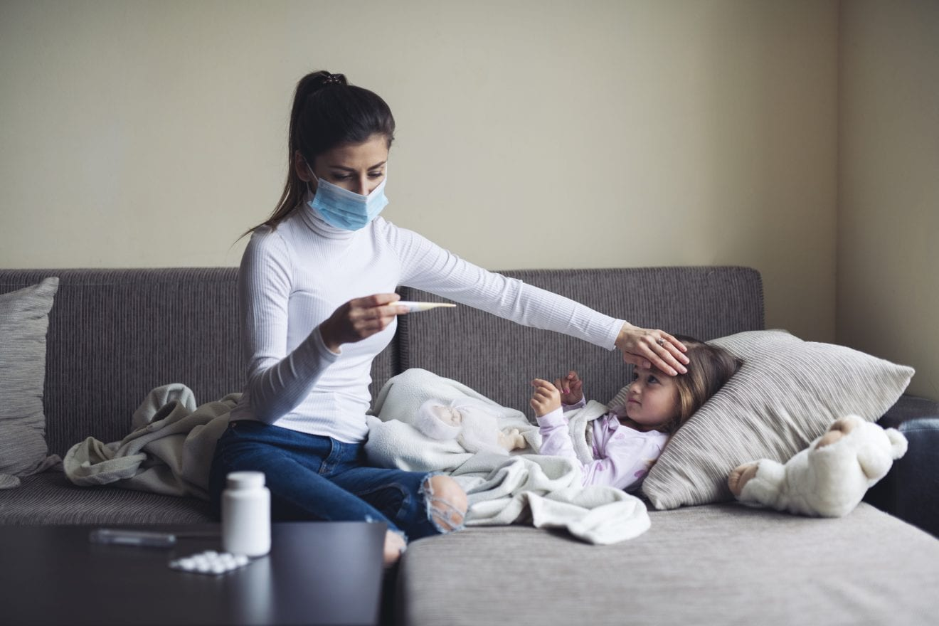 Mother wearing face protection mask at home and measure a temperature on her sick child.