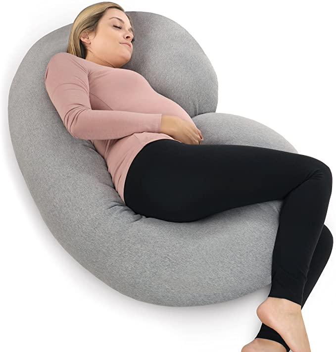 woman lying down with a pregnancy pillow
