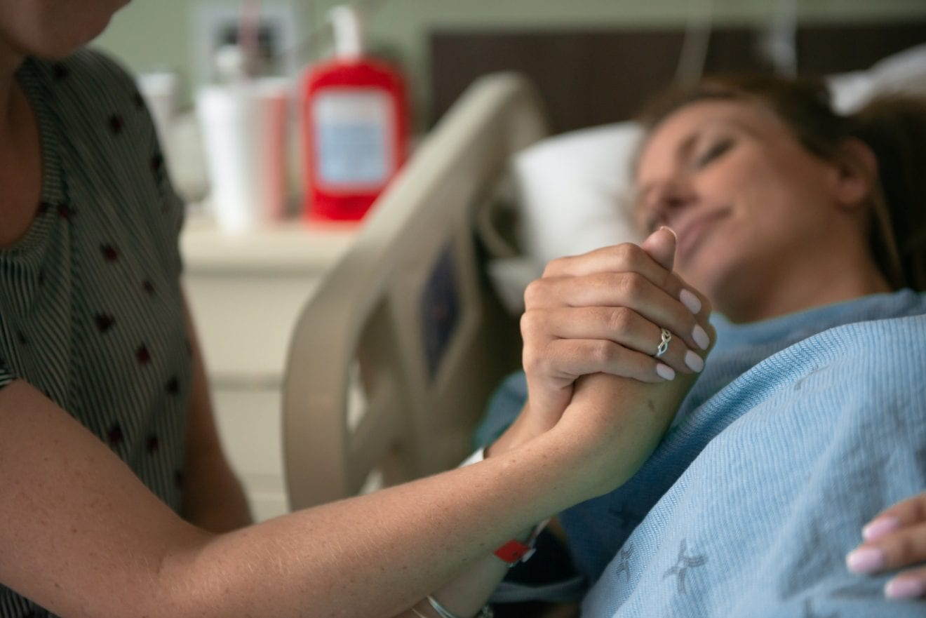 A woman holds the hand of a support person while in the throws of labor and trying to work through the pain of contractions.