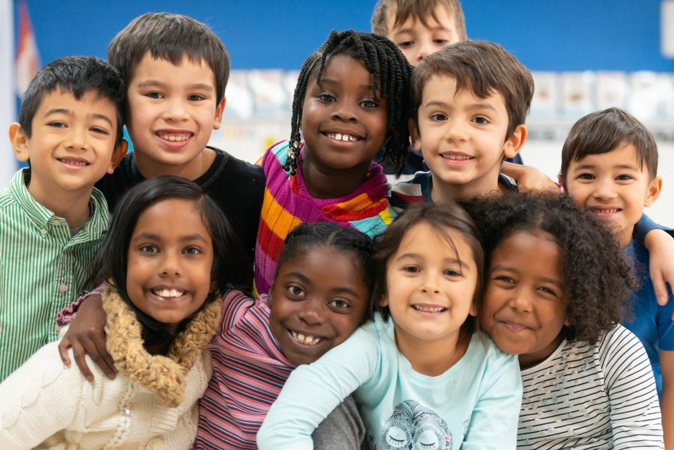 A group of culturally diverse kids stacked on top of each other while cuddling in close and showing how happy they are.