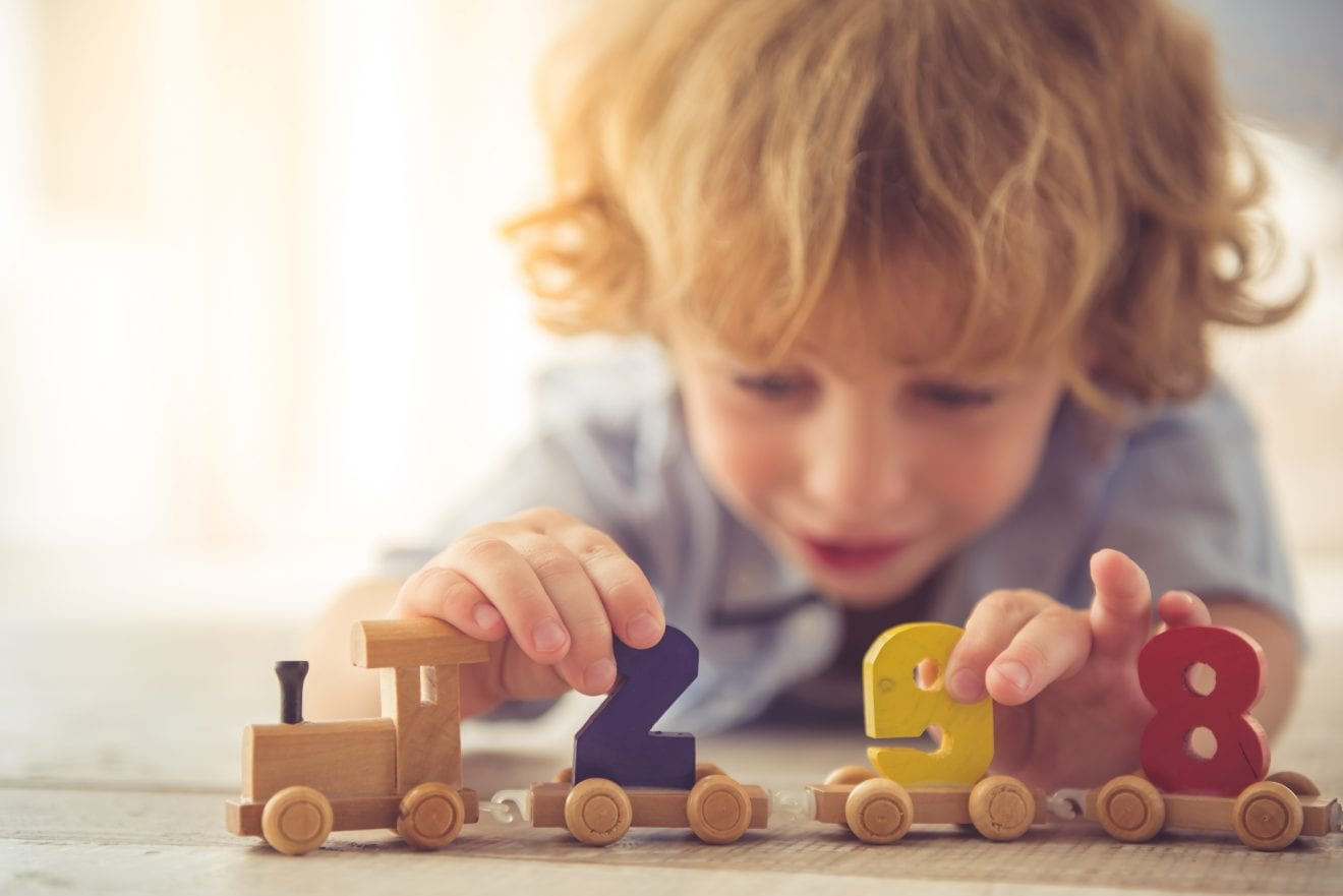 Cute little boy is playing with toy wooden train and numbers at home.