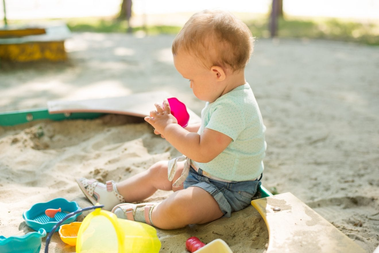 Cute toddler girl playing in sand on outdoor playground. Beautiful baby having fun on sunny warm summer day. Child with colorful sand toys.