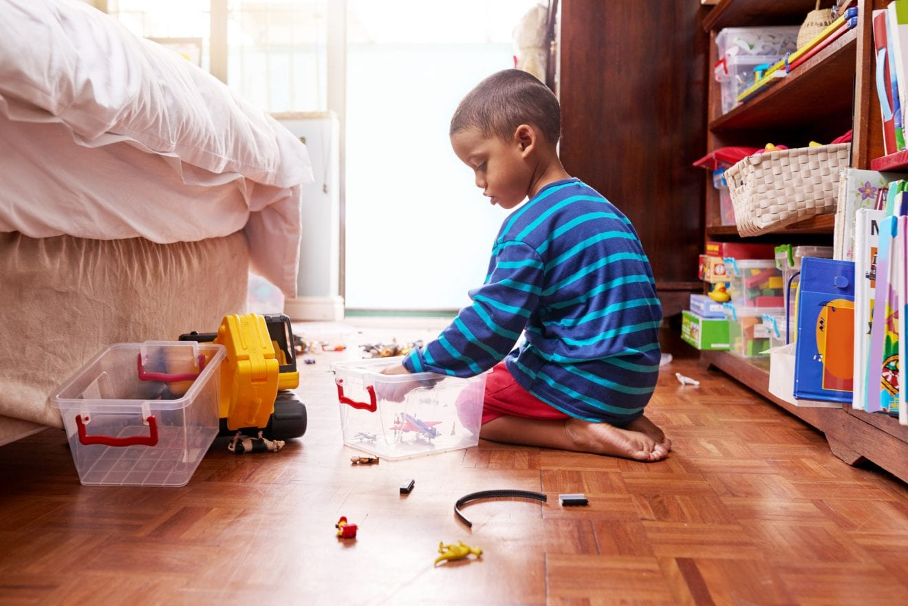A young boy sitting on the floor picking up his toys in a bedroom.