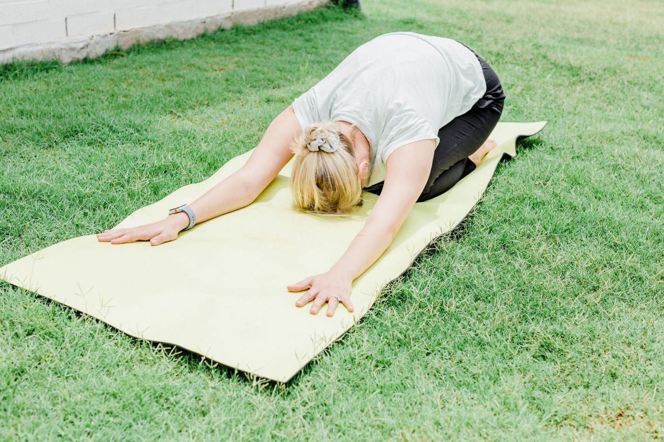 A woman laying on her yoga mat doing child's pose.