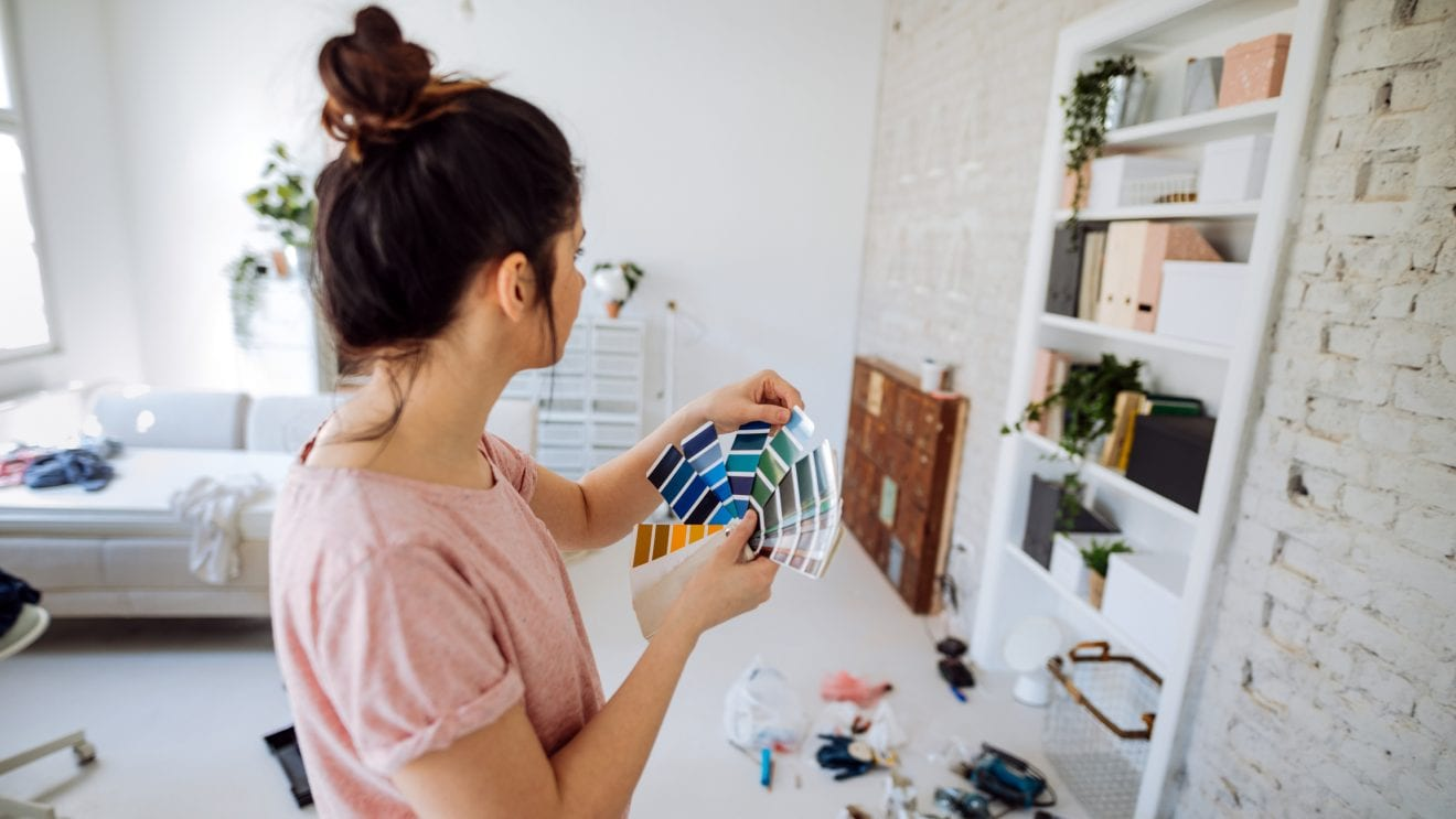 Young woman during reconstruction of apartment, holding color chart and choosing the right color for the wall.