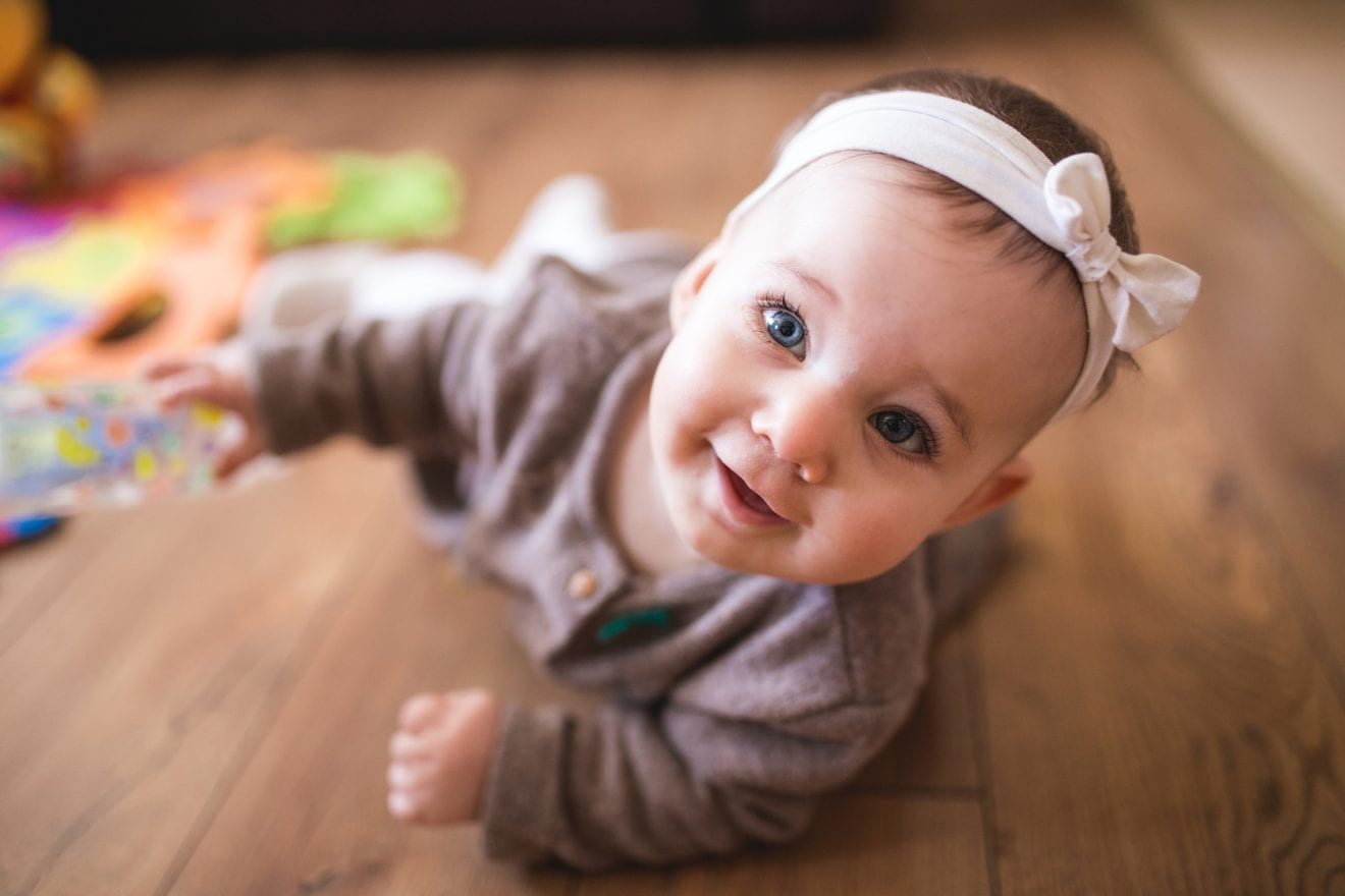 Adorable Baby Girl Learning How To Crawl At Her Warm Home