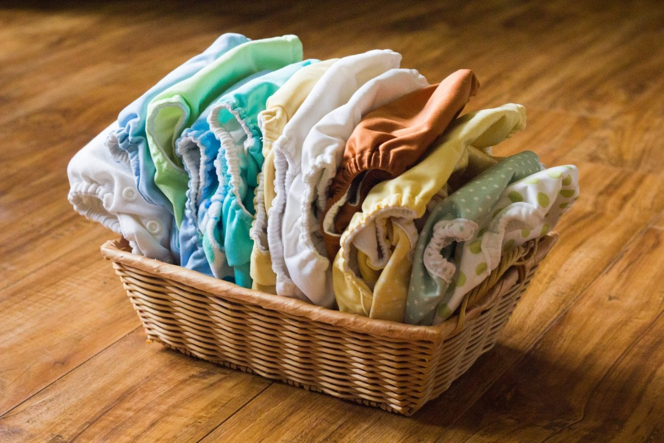 A display of varying colors, shapes and sizes of cloth diapers arranged in a small rectangle shaped basket on a wooden surface.