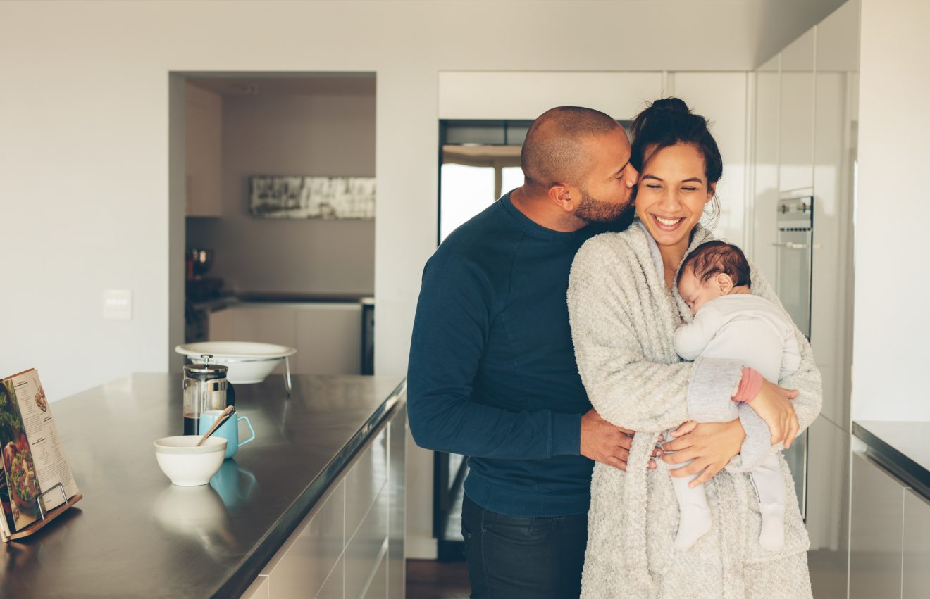Man kissing his wife holding a newborn baby boy in kitchen.