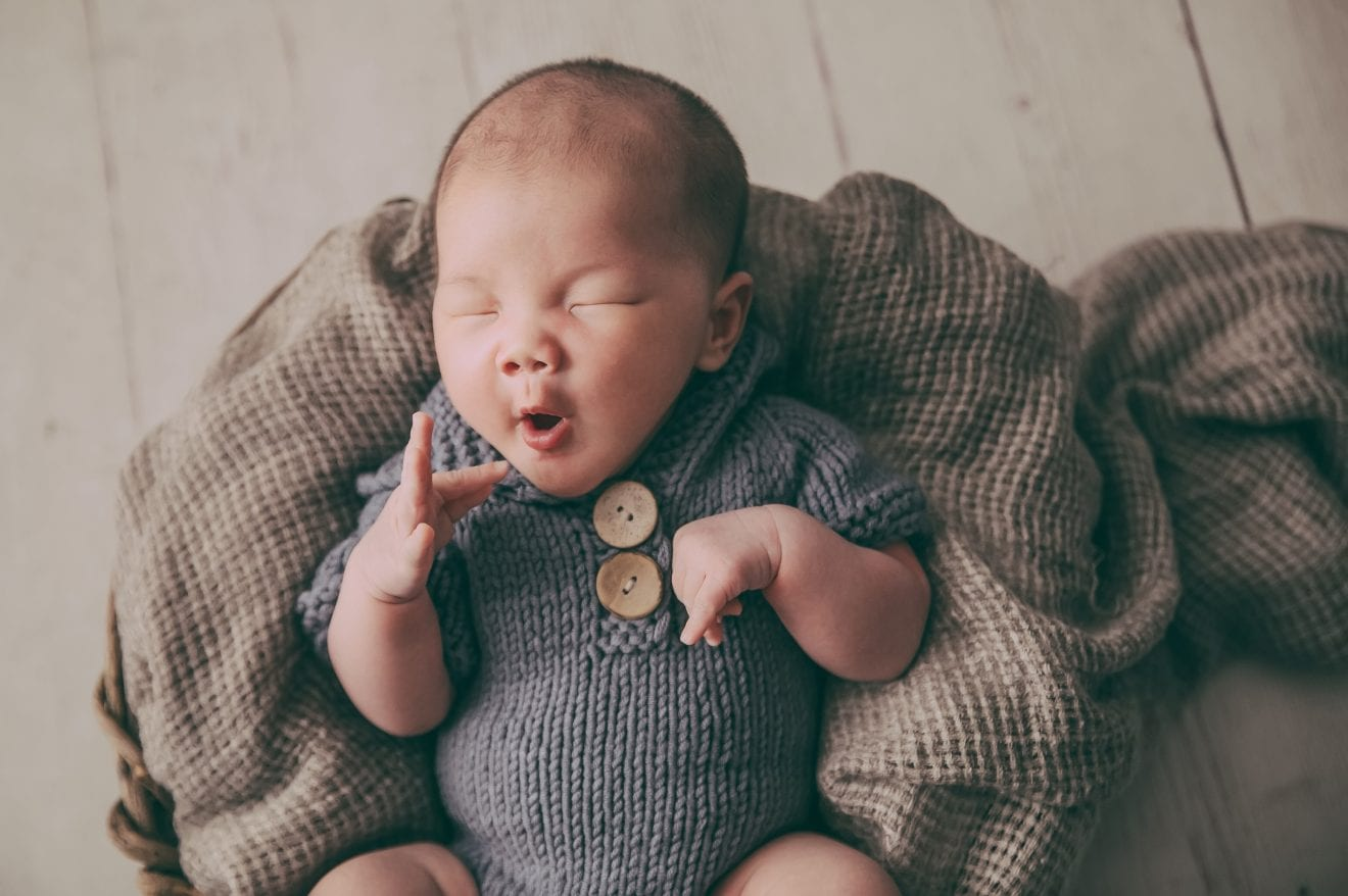 Sleepy newborn baby boy about to yawn.