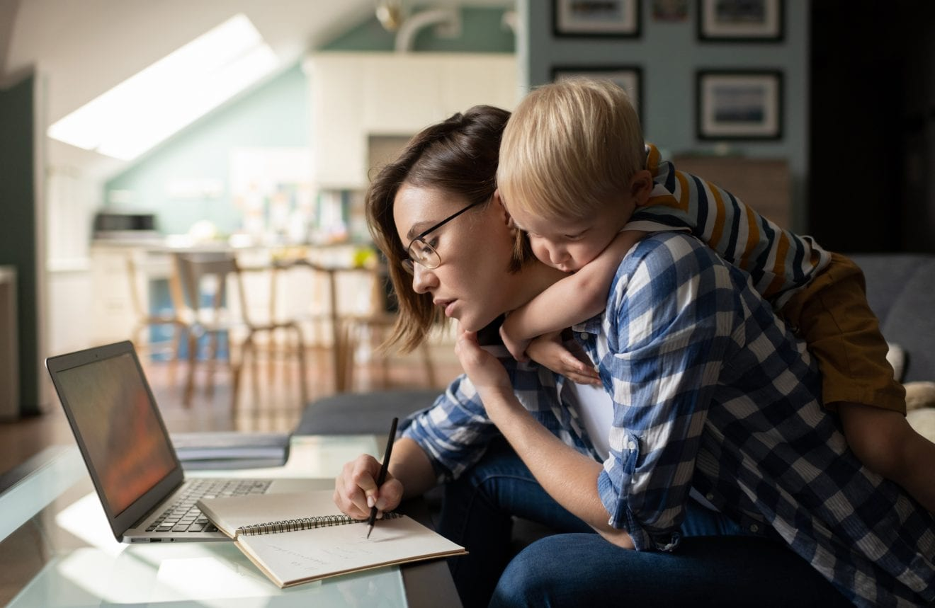 Side view of busy female in casual clothing studying with laptop and writing notes with little boy is hugging her while standing behind her on sofa in the living room.