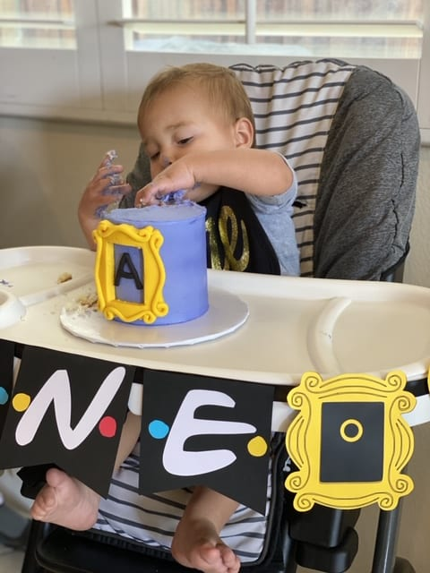 Twin baby boy eating his Friends smash cake