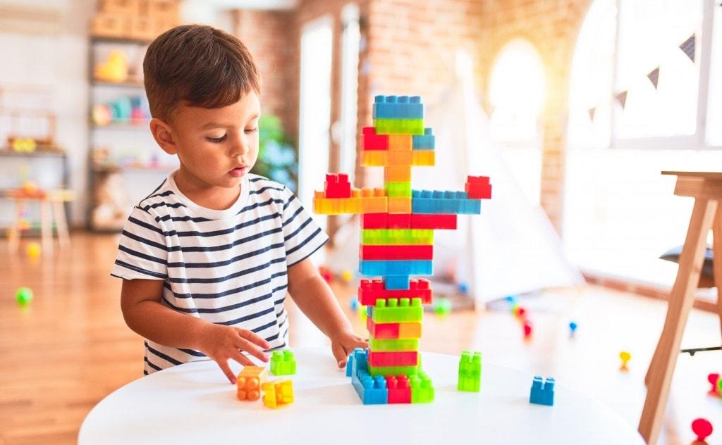 Beautiful toddler boy playing with construction blocks at kindergarten.
