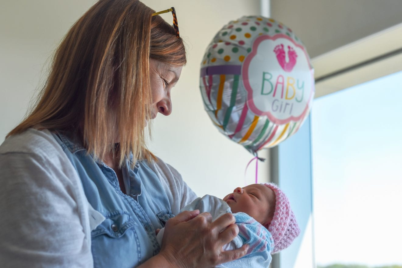 Happy woman visiting baby in hospital.