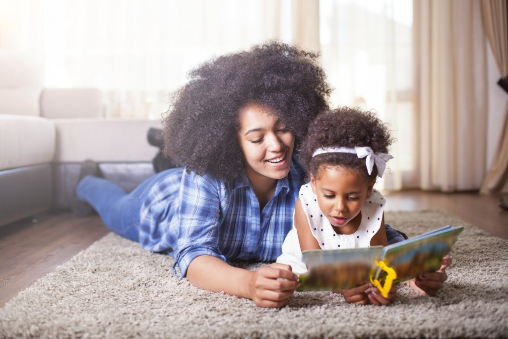 Mother reading a book to her daughter on carpet.