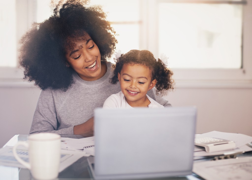 Young mother working and spending time with her daughter