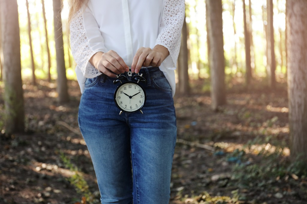 Woman with alarm clock in the woods.