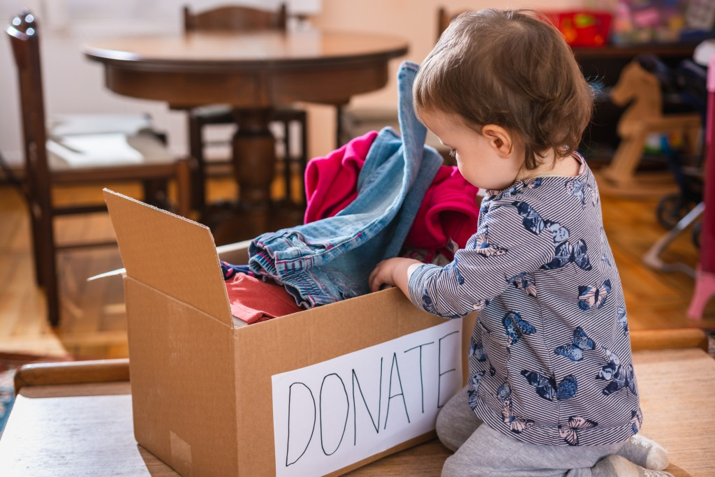 Child sorting clothes for donation