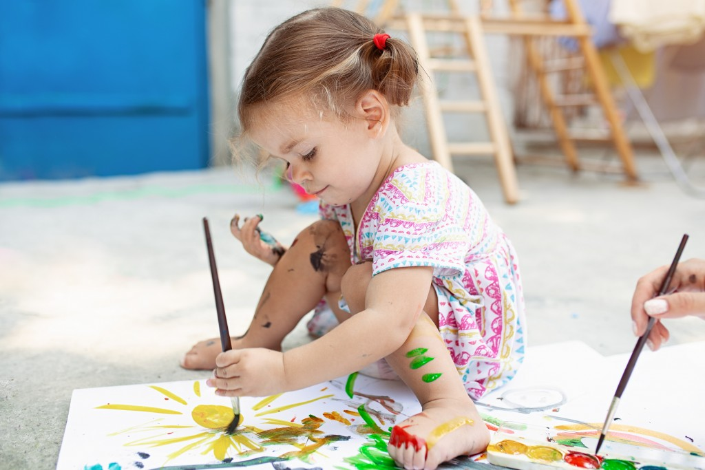Cute little caucasian Girl enjoying Painting at the backyard with paper, water color and art brush.