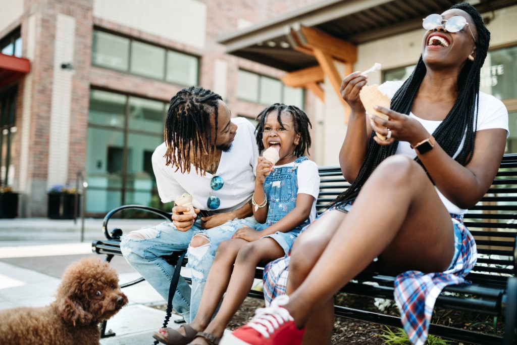 A cute young African American family enjoys relaxation time in the city with ice cream cones on a hot summer day.