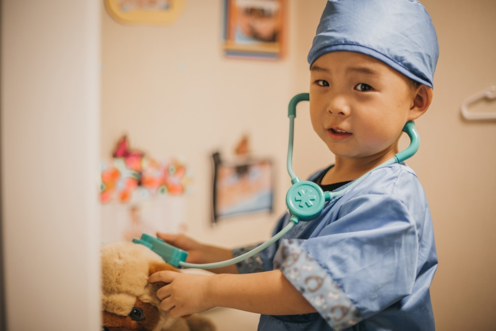 Little boy dressed up as a doctor or vet taking care of his teddy bear patient.