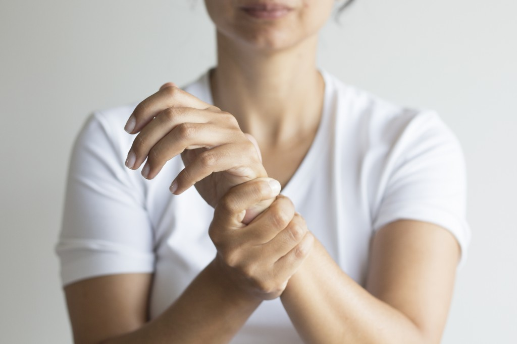 Woman holding wrist due to carpal tunnel syndrome.