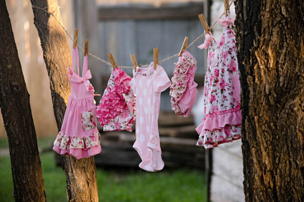 Clean, pink floral, and polka-dotted clothes on the clothesline outside.