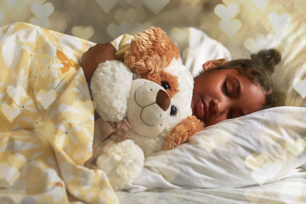 Shot of an adorable young girl sleeping peacefully in her bed cuddled up with her stuffed animal.