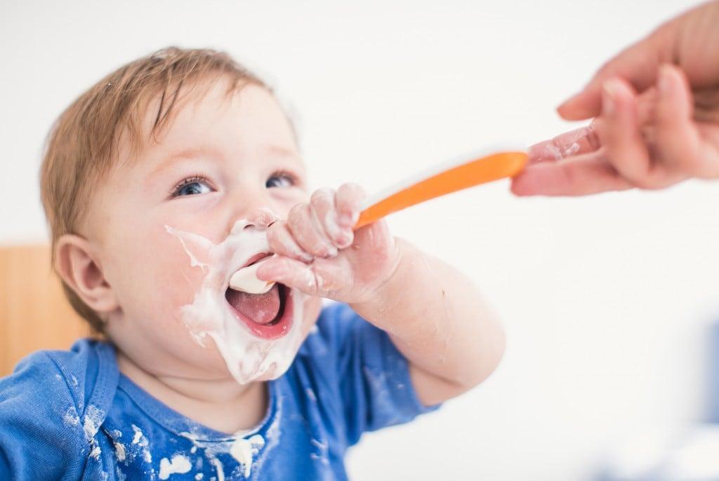 Unrecognizable Person Giving Yogurt To a Baby Boy