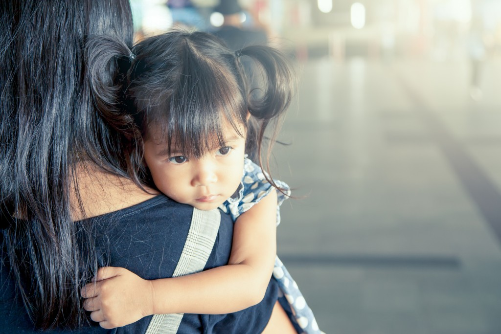 Mother and child,cute little girl resting on her mother's shoulder in the train station.