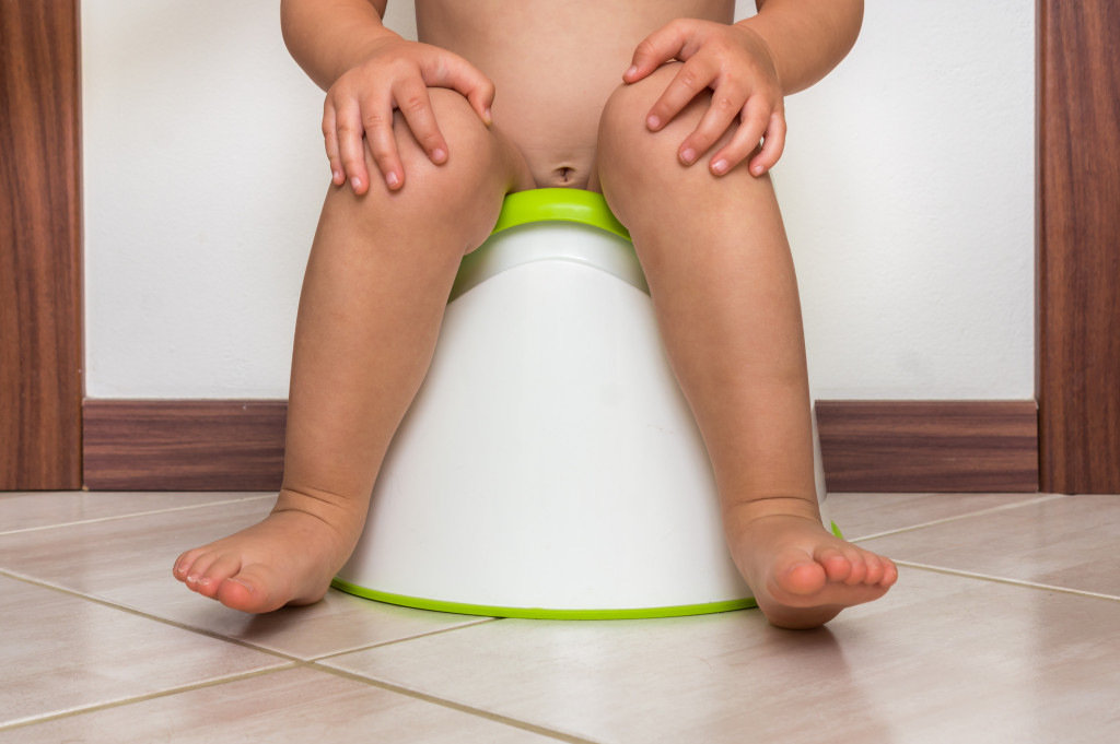 Child is sitting on baby potty - toilet training concept
