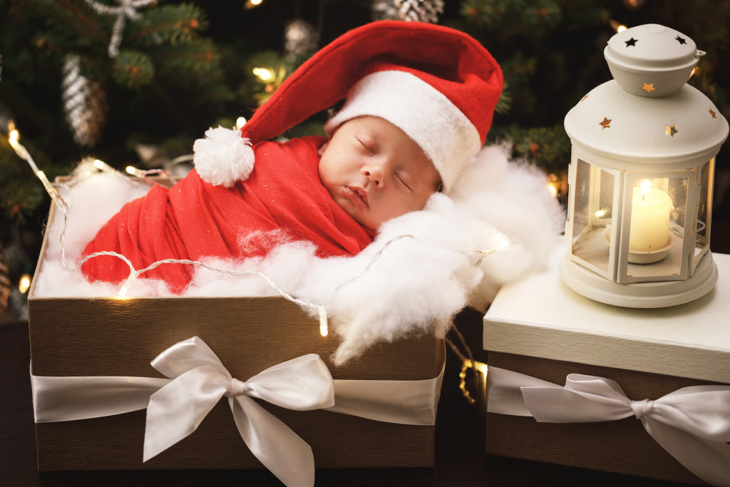 Cute newborn baby wearing Santa Claus hat is sleeping in the xmas gift box.