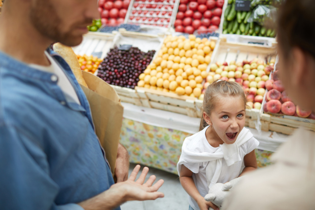 High angle view at spoiled little girl screaming at parents in supermarket.