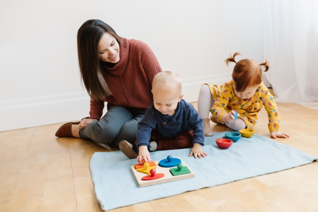 Theresa from Montessori in Real Life sitting on the floor with her kids doing Montessori work.