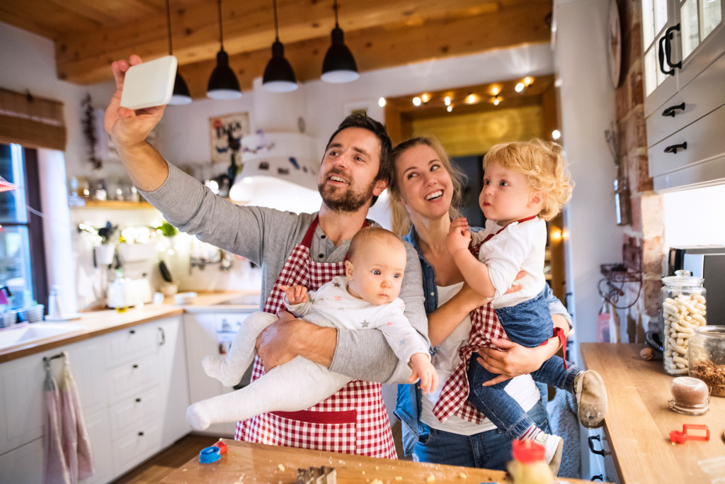 Beautiful young family making cookies at home. Father, mother, toddler boy and baby taking selfie with a smartphone.