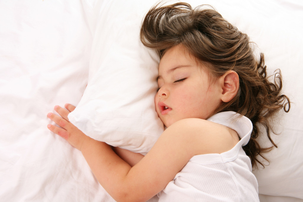 Little girl sleeping on a white bed with her pillow