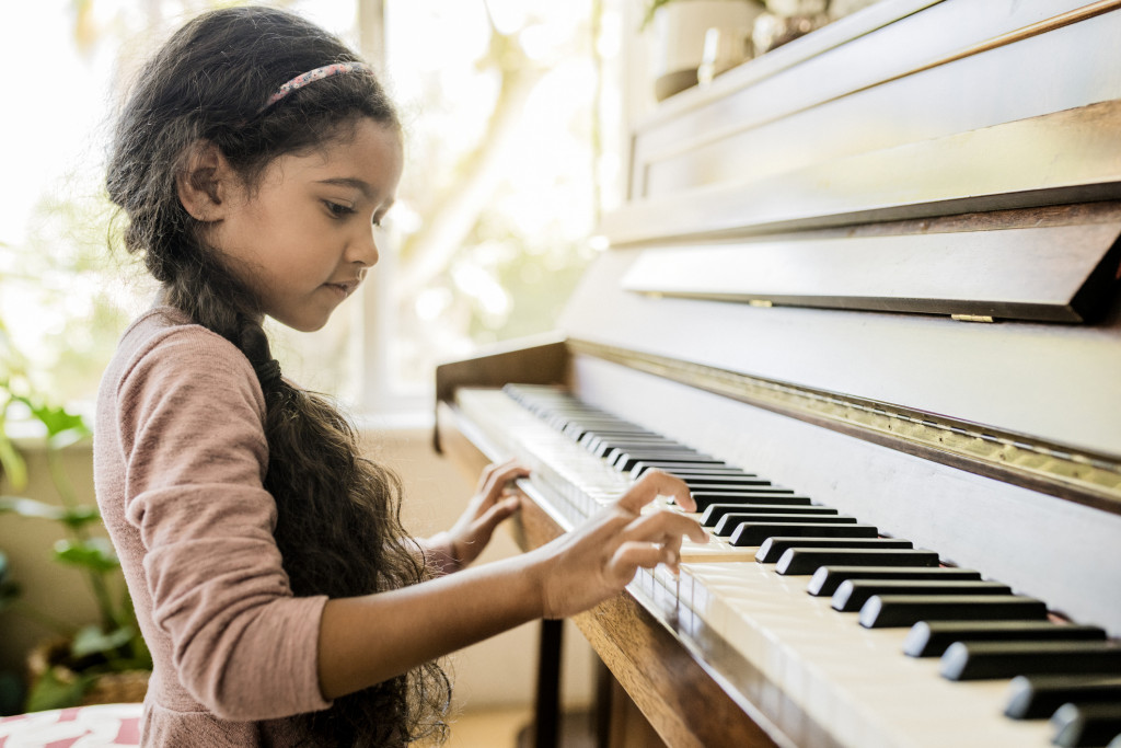 Side view of a girl playing the piano.