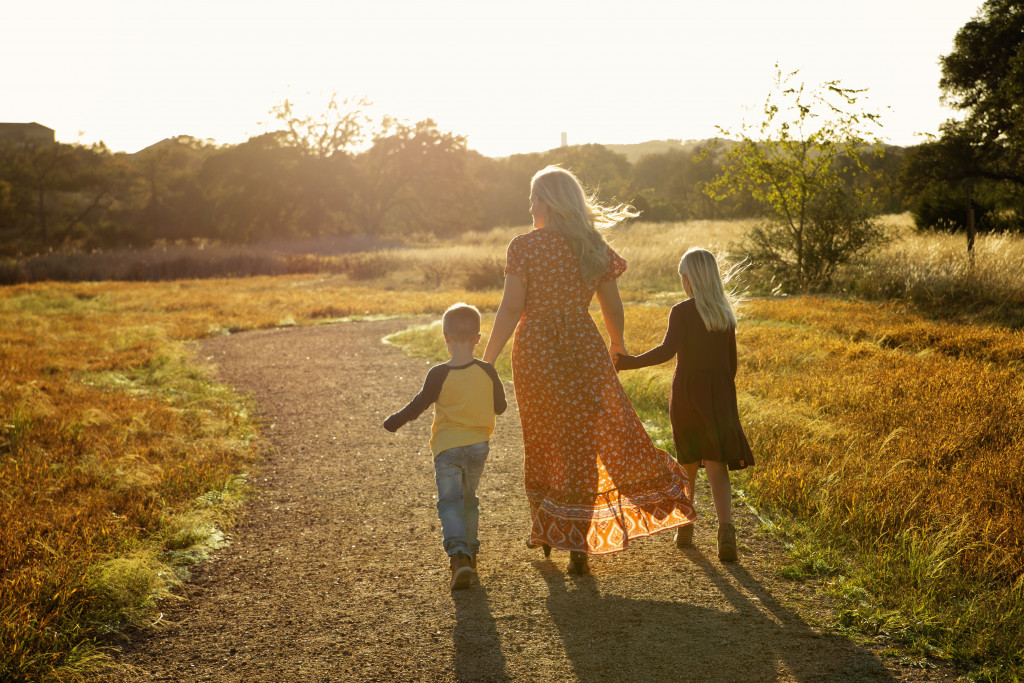 Young widow mother holding her children's hands as they walk off into the sunset.